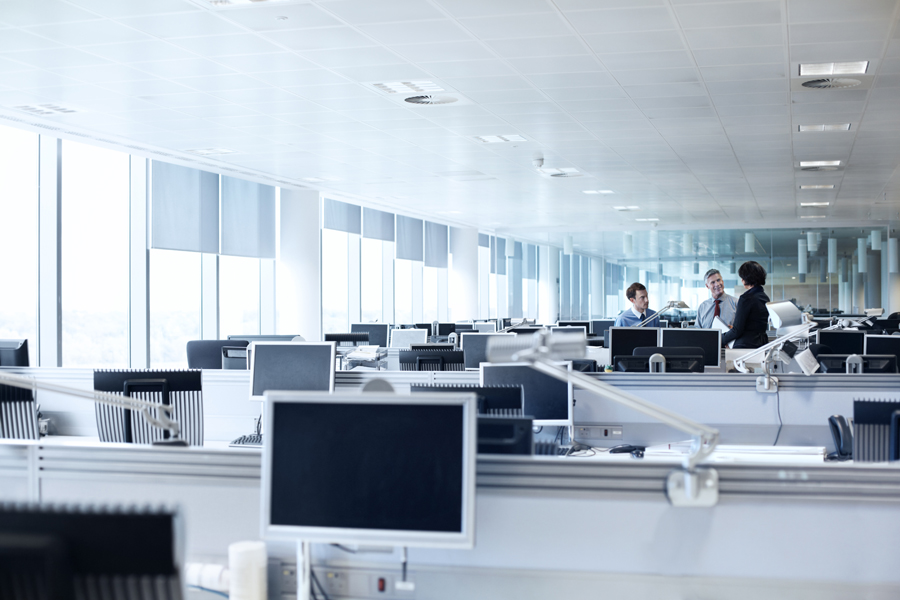 Rows of white computer screens in large openplan office