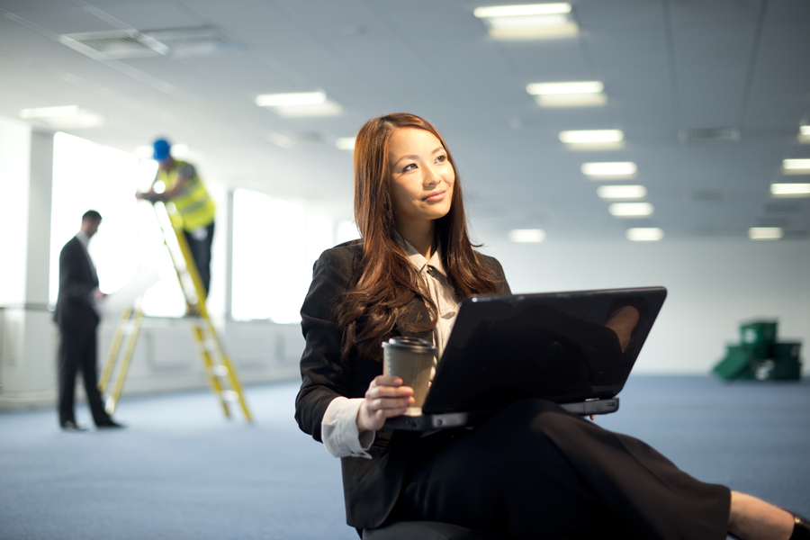 young businesswoman in empty office with contractors making alterations